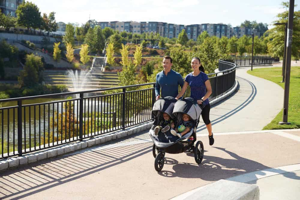 Janet and Jeff running in the park with their son in a new jogging stroller.