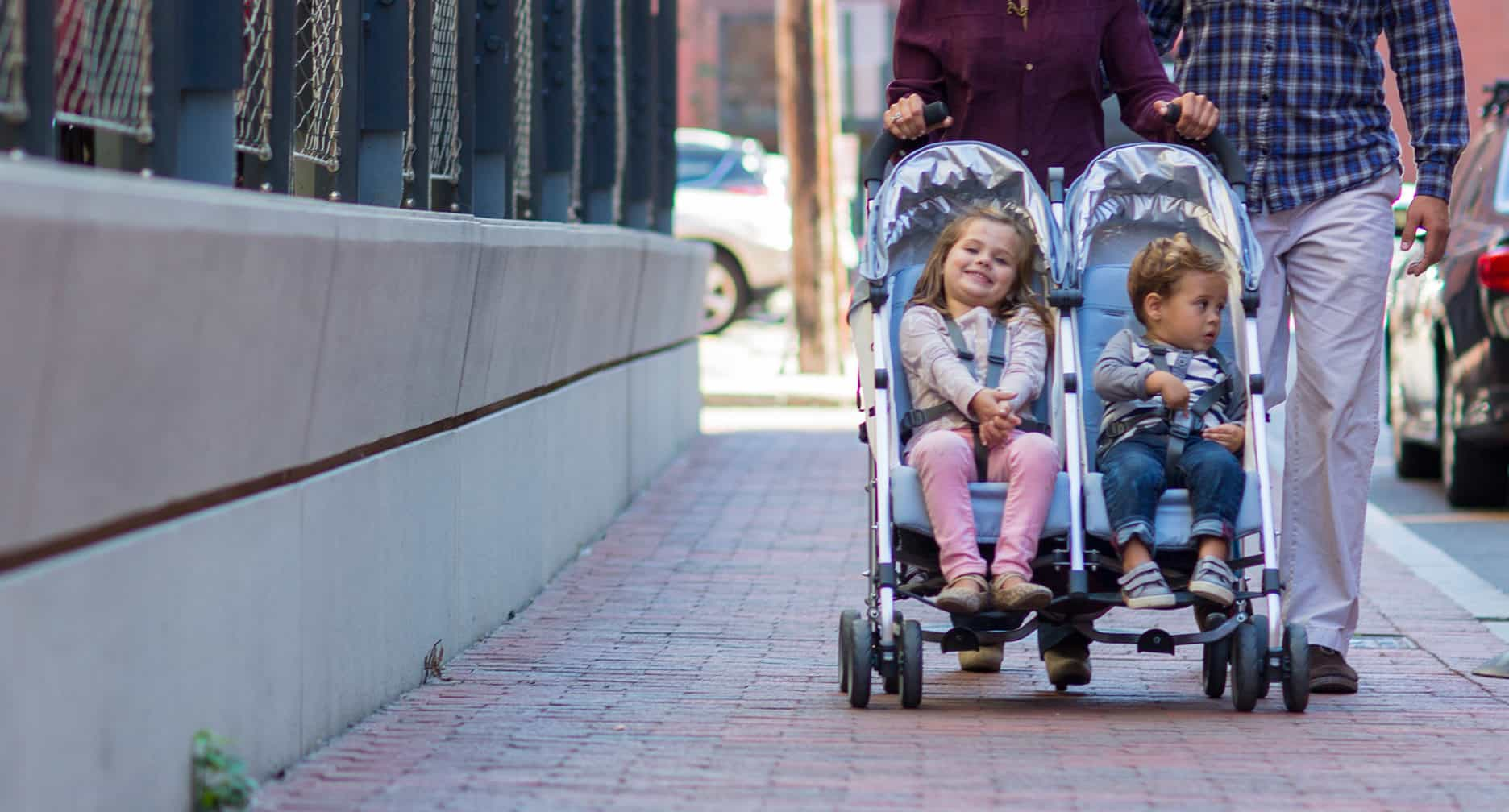 A couple and their children walking through the city with the best double umbrella stroller.
