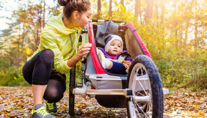 Beautiful young mother with her daughter running with the best jogging stroller.